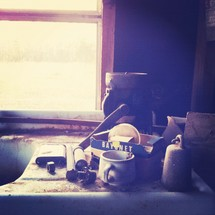 coffee cup, coffee grinder, and junk beside a sink