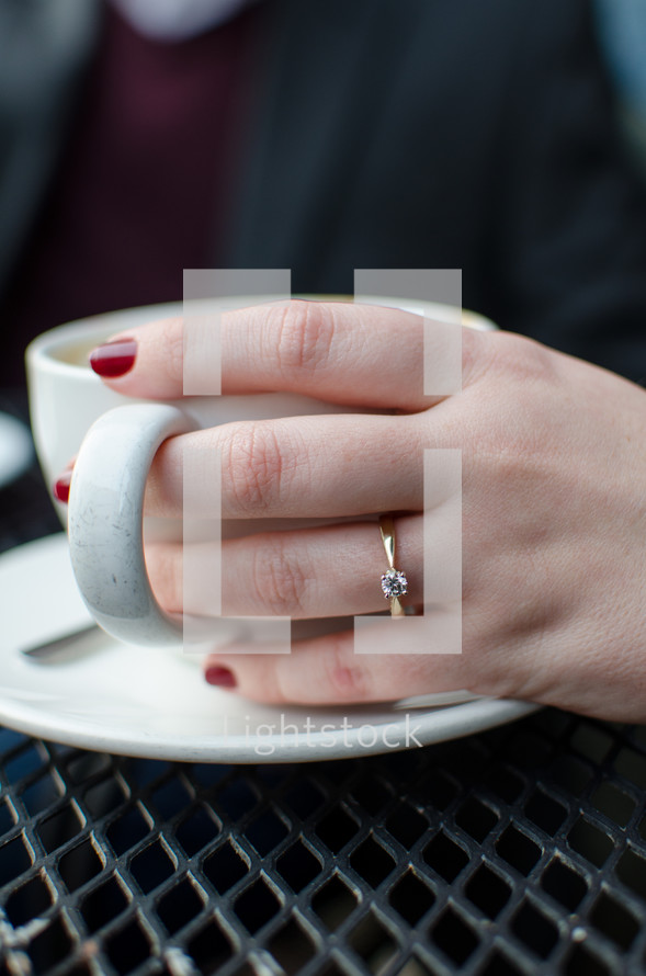 a woman with hand on a mug with engagement ring