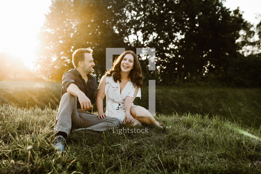 a couple sitting in the grass