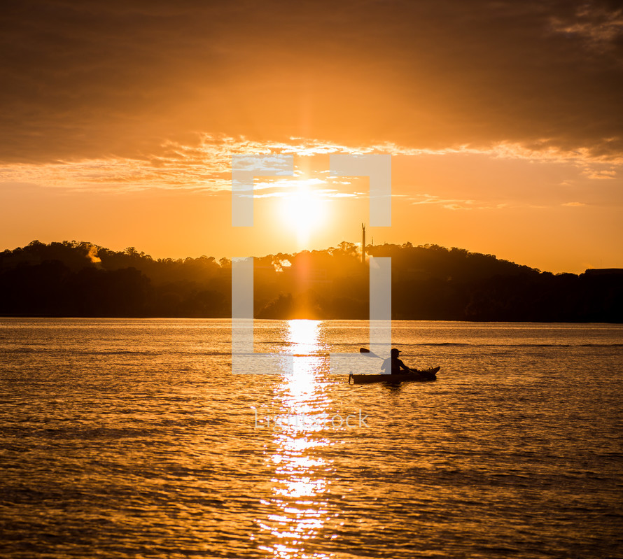Silhouette of a canoe on the ocean water at sunset.