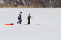 children dragging a sled in snow