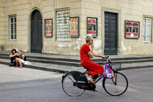 Elderly woman riding bicycle while smoking