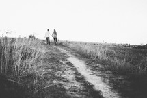 a couple walking on a dirt road