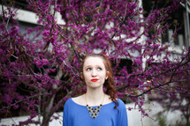 a teen redhead posing for a portrait in front of purple flowers on a tree