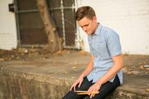 Teen boy sitting on  the sidewalk ledge holding drum sticks.
