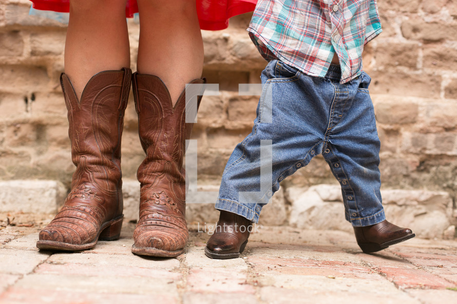 The feet of a woman and baby wearing cowboy boots