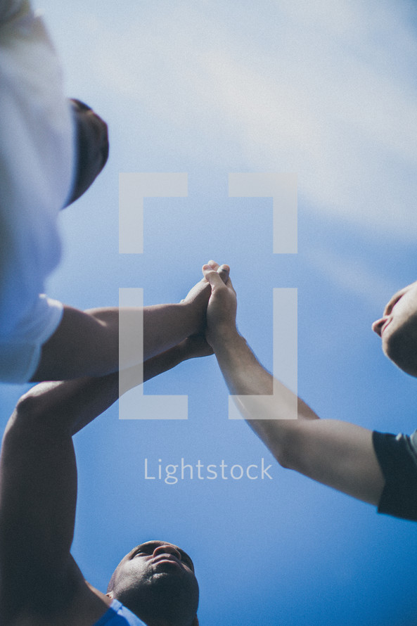 athletes with hands together in prayer