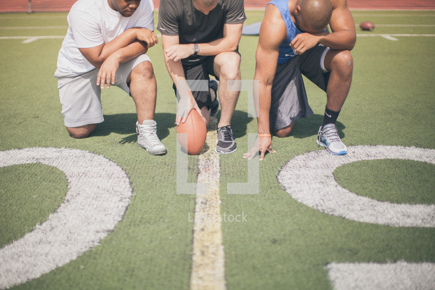 athletes kneeling in prayer on the football field