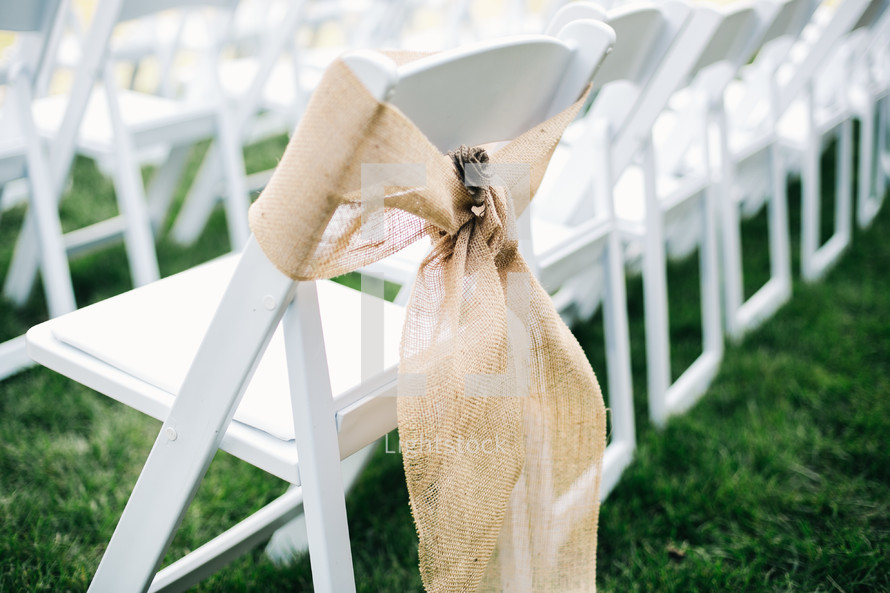 burlap ribbon around white folding chairs for an outdoor wedding