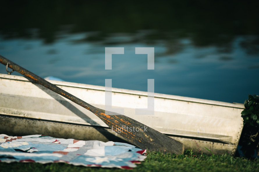 row boat next to a blanket in the grass