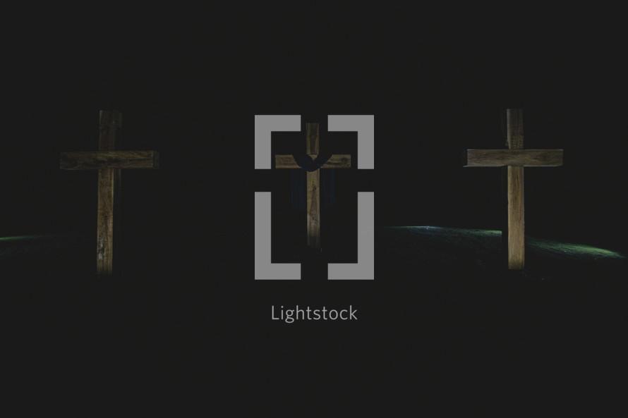 three crosses in darkness