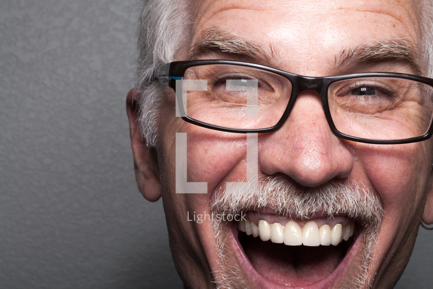 The face of a laughing, middle aged man wearing glasses.