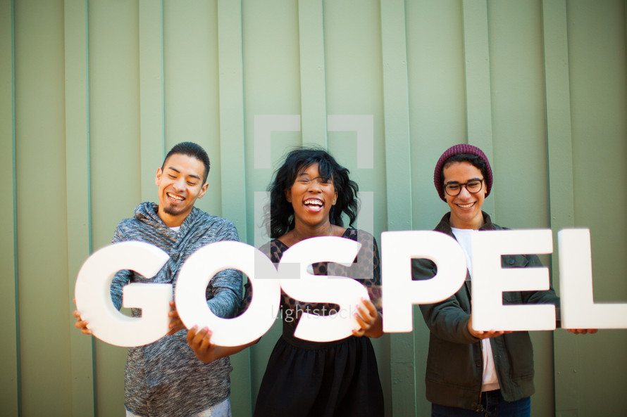 """Three smiling people holding a sign saying, """"gospel."""""""