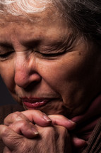 An older woman praying.