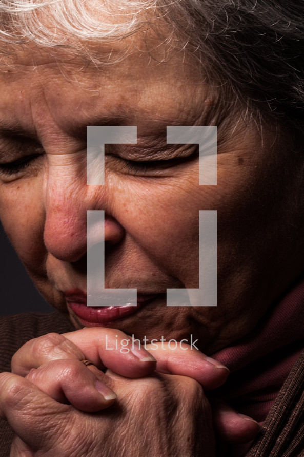 An older woman praying.