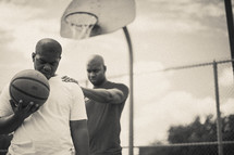 Men in prayer on a basketball court holding a basketball.