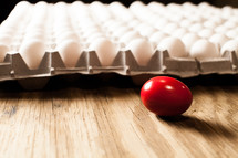 Cartons of white eggs with one red egg on a wood table.