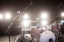 Stage lights shine on a drum set and microphones.