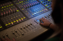 A woman manipulates a sound board.