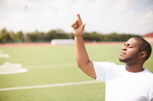 man on a football field pointing up to God