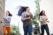 teen girls running down a street carrying cellphones