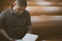 man holding a hymnal