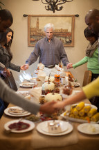 family holding hands in prayer at a Thanksgiving dinner table