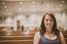 woman smiling sitting in a church pew