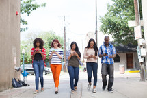 young adults walking and texting