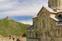 Orthodox church and monastery by a grassy hill.