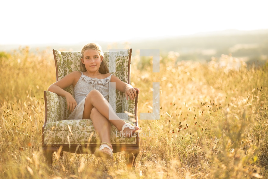 young girl sitting in a chair in a field