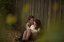 Couple hugging beside a wooden fence