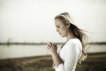 A young woman praying at the edge of a lake