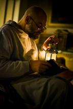 Sittiing man reading Bible holding lantern.