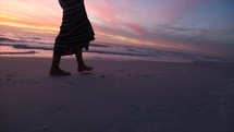 girl walking on a beach at sunset