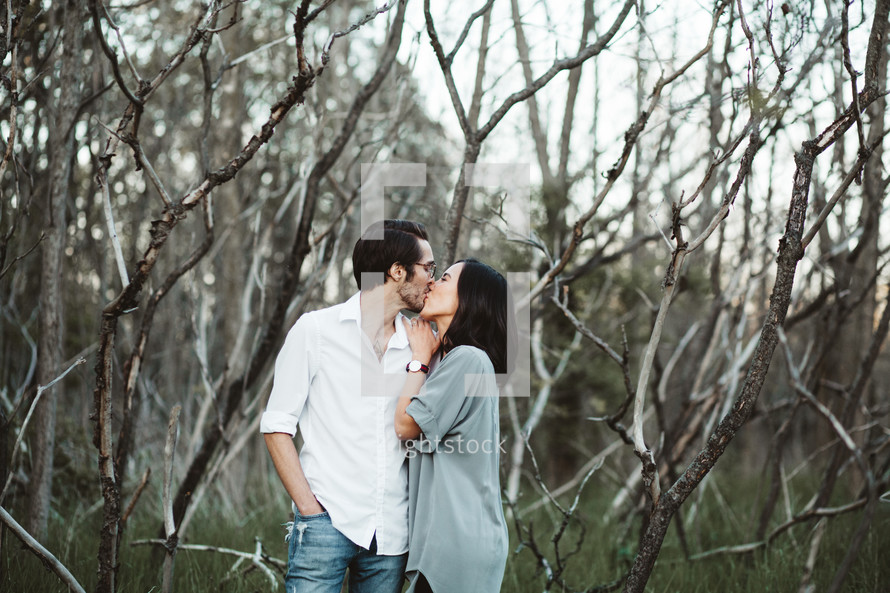 a couple kissing in the woods
