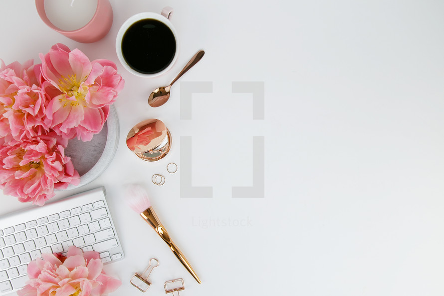 pink spring flowers, computer keyboard, makeup brush, gold hand mirror, rings, coffee mug, and gold spoon on a white background