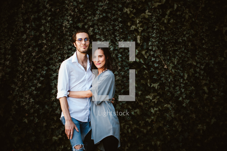 a couple standing together in front of an ivy covered wall