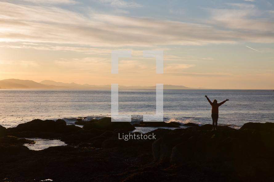 a person standing on a shore with arms raised