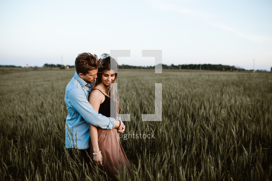 a couple snuggling in a field of wheat