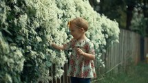 a toddler girl picking flowers