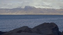 snow on mountains at the edge of a shore