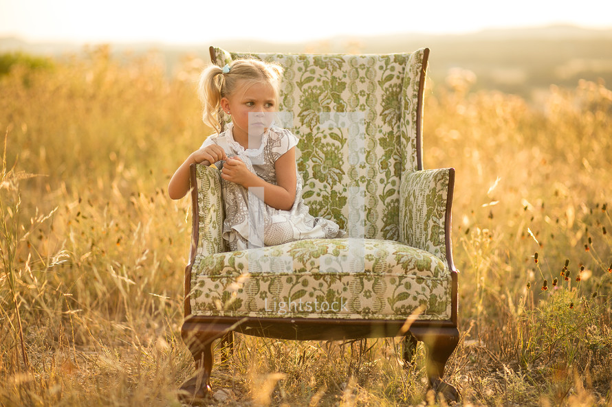 young girl in pigtails sitting in chair in a field