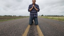 man in prayer on the center lines of a lonely road