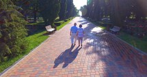 Aerial footage of senior couple walking holding hands outdoors in summer park. 4k