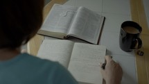 a woman reading a Bible and taking notes