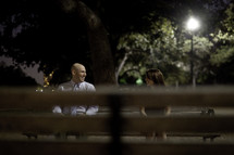 couple sitting on a park bench at night looking at each other