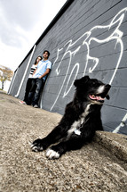 teens standing against a graffitied wall and a dog