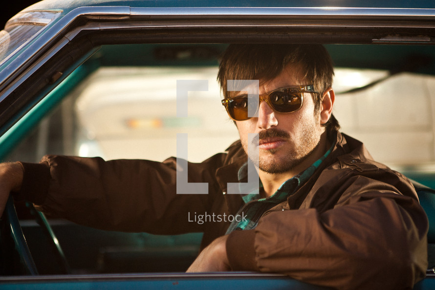 man in sunglasses looking out of a car window