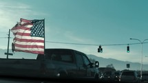 American flag waving on the back of a pickup truck